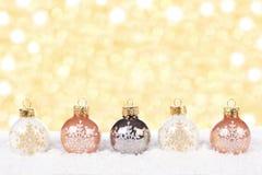 Vita och guld- julprydnader i snö Royaltyfria Foton