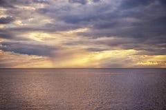 Vita och guld- strålar för sol` s gör deras väg till och med molnen Royaltyfri Fotografi