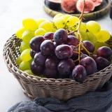 Vita och mörka druvor i en korg Arkivfoto
