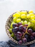 Vita och mörka druvor i en korg Fotografering för Bildbyråer