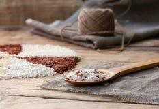 Vita och röda ris i en träsked Arkivbilder