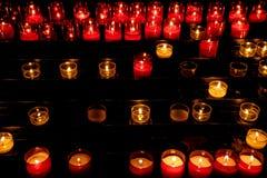 Vita och röda tända stearinljus i kyrka i mörker royaltyfri bild