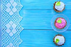 Vita och rosa bakelser, snör åt och blå bakgrund royaltyfria foton