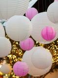Vita och rosa lightballs som hänger på ett tak Arkivbild