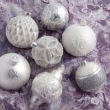 Vita och silverjulbollar på inpackningspapper Arkivfoton