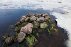 Vita is- och snöstycken med flera stenar i flodkustvatten i kall vintermorgon Royaltyfri Foto