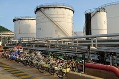 Vita olje- behållare och cyklar som parkerar i Chonburi, Thailand Arkivfoto