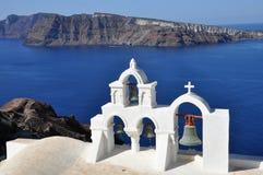 Vita ortodoxa kyrkliga klockor i den Santorini ön, Grekland, sikt till santorinicalderaen Royaltyfri Fotografi