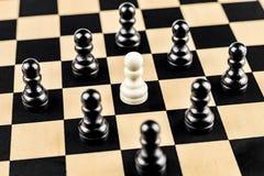 Vita Pawn som omges av fiender royaltyfri foto