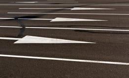 Vita pilar och linjer på sprucken asfalt ytbehandlar Arkivfoton