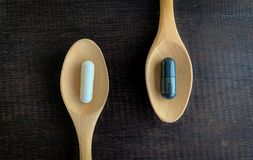 Vita piller och svarta piller förläggas på en träsked som förläggas på det gamla trät royaltyfri fotografi
