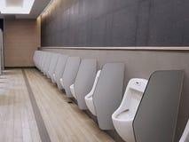 Vita pissoar med delningar inom mäns toalett arkivbilder