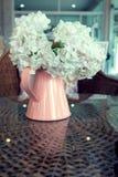 Vita plast- blommor i rosa blommavas på rottingen väver Arkivbilder