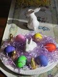 Vita porslinkaniner, mångfärgade hårda kokta ägg och små chokladkaniner, oj mitt! arkivfoto