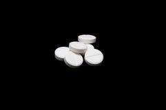 Vita preventivpillerar isoltaed på svart Arkivbilder