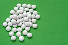 Vita preventivpillerar på grön bakgrund arkivbilder