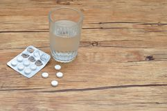 Vita preventivpillerar som visas med ett exponeringsglas av vatten och en blåsapacke royaltyfria bilder