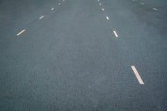 Vita prickiga linjer markering på naturlig bakgrund för asfalt Körbanalinje arkivfoto