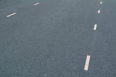 Vita prickiga linjer markering p? naturlig bakgrund f?r asfalt K?rbanalinje arkivbild