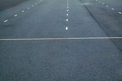 Vita prickiga linjer markering p? naturlig bakgrund f?r asfalt K?rbanalinje royaltyfri fotografi