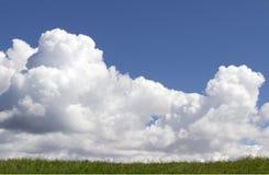 Vita pösiga moln för djupblå himmel över kullen för grönt gräs Royaltyfri Fotografi