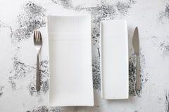 Vita rektangulära plattor med gaffeln och kniven på vit träbac Arkivbild