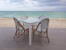 Vita restaurangstångtabell och stolar nära stranden i Bahamas arkivfoton