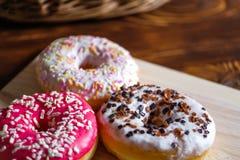 Vita, rosa och bruna glasade donuts p? tr?korg f?r bakgrund och n?ra rotting arkivfoton