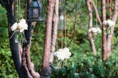 Vita rosor i en exponeringsglasvas som hängs i ett gifta sig parti - royaltyfria bilder