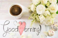 Vita rosor, kaffe och anmärkning för bra morgon Arkivfoto
