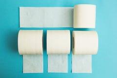 Vita rullar av toalettpapper på en blå bakgrund arkivfoton