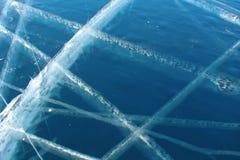 Vita skärande linjer på mörkblå genomskinlig is arkivbilder