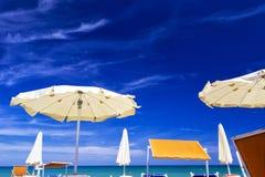 Vita slags solskydd med blå himmel och moln för sommarseascapebegrepp Royaltyfri Bild