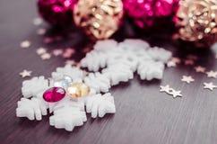 Vita snöflingor på bakgrund av magentafärgade och guld- xmas-struntsaker Royaltyfria Bilder