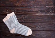 Vita sockor för ett par med ljus - blå remsa på en träbakgrund Royaltyfria Foton