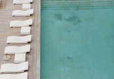 Vita sol-dagdrivare och deckchairs bredvid simbassängen med crystal blått vatten Royaltyfria Bilder