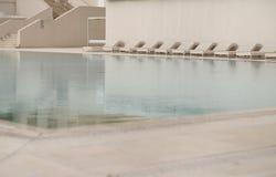Vita sol-dagdrivare och deckchairs bredvid simbassängen med crystal blått vatten Royaltyfria Foton