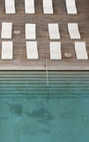 Vita sol-dagdrivare och deckchairs bredvid simbassängen med crystal blått vatten Royaltyfri Fotografi