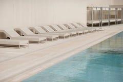 Vita sol-dagdrivare och deckchairs bredvid simbassängen med crystal blått vatten Fotografering för Bildbyråer