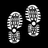 Vita spår från skor på en svart bakgrund Arkivbild
