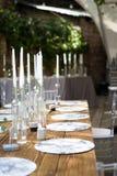 Vita stearinljus i flaskor av vinställningen på den vita tabellen royaltyfria bilder