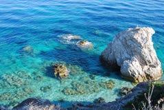 Vita steniga utlöpare blåtten och det kristalliska havet arkivfoto
