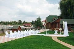 Vita stolar för gäster står för bröllopaltaret på en ope Royaltyfri Fotografi