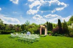 Vita stolar framme av den härliga bröllopbågen Arkivfoto