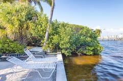 Vita stolar längs en härlig kust semestrar begrepp Arkivbilder