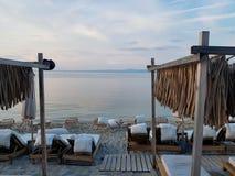 Vita stolar och sängar på kust nära det härliga blåa havet arkivfoto