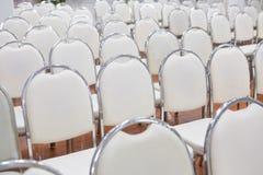 Vita stolar ordnade i ett seminariumrum royaltyfri fotografi