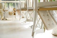 Vita stolar på tabeller som är uppochnervända på gatakafésommar, terrasserar Royaltyfri Bild