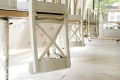 Vita stolar på tabeller som är uppochnervända på gatakafésommar, terrasserar Royaltyfria Foton
