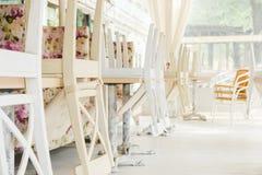 Vita stolar på tabeller som är uppochnervända på gatakafésommar, terrasserar Arkivfoton